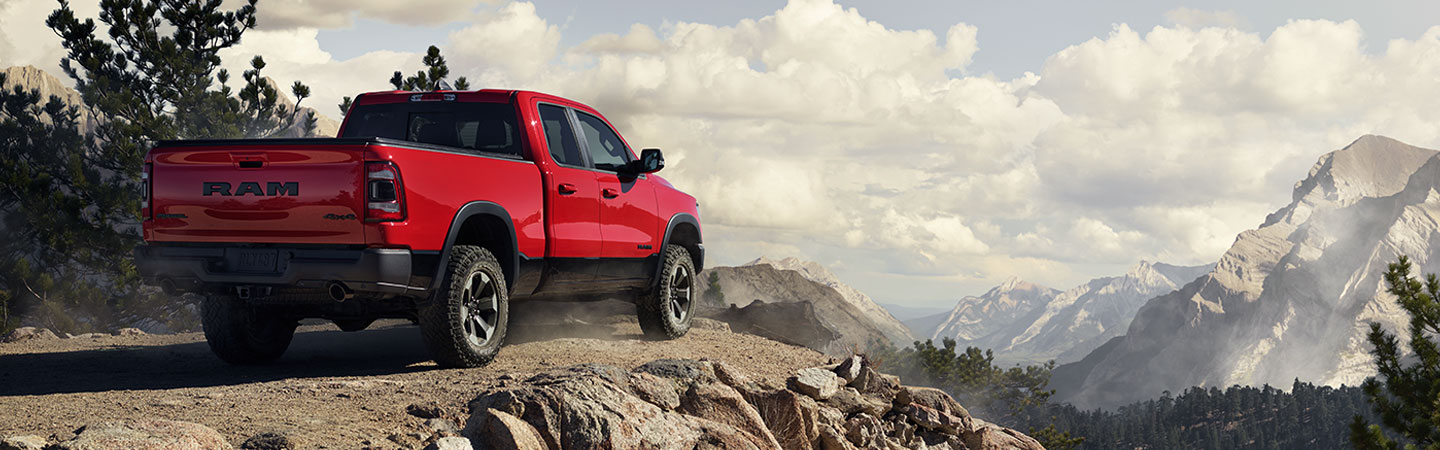 Rear view of a red 2021 RAM 1500 parked at a cliff overlooking the mountains