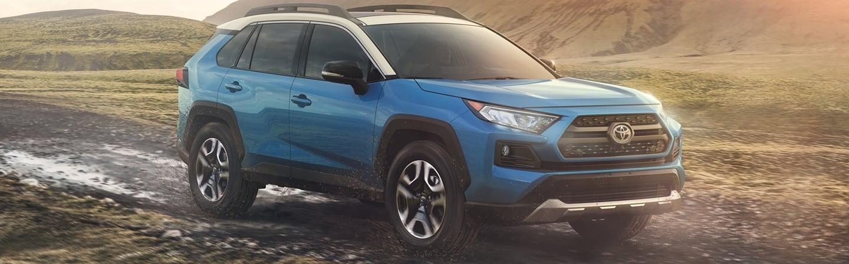 Blue 2020 Toyota RAV4 driving through mud