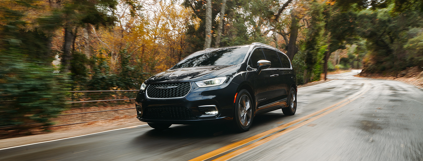 Front view of a black 2021 Chrysler Pacifica driving down the road
