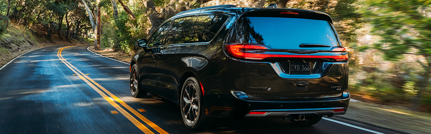 Rear view of a black 2021 Chrysler Pacifica driving down the road