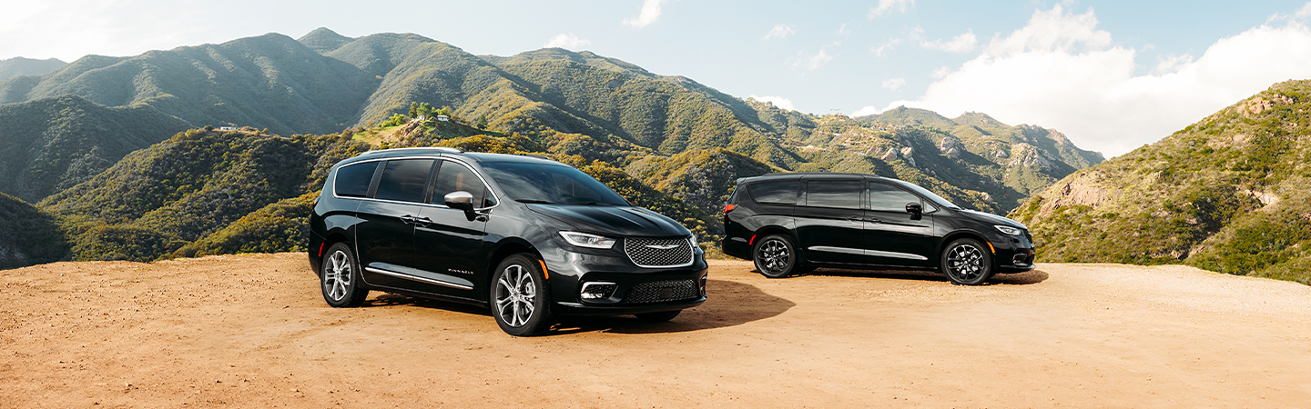 Side views of two black 2021 Chrysler Pacifica vehicles parked in the mountains