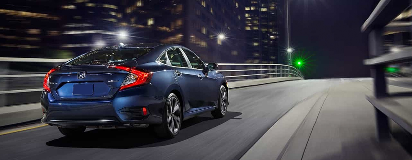 2019 Honda Civic driving in the city rear view.