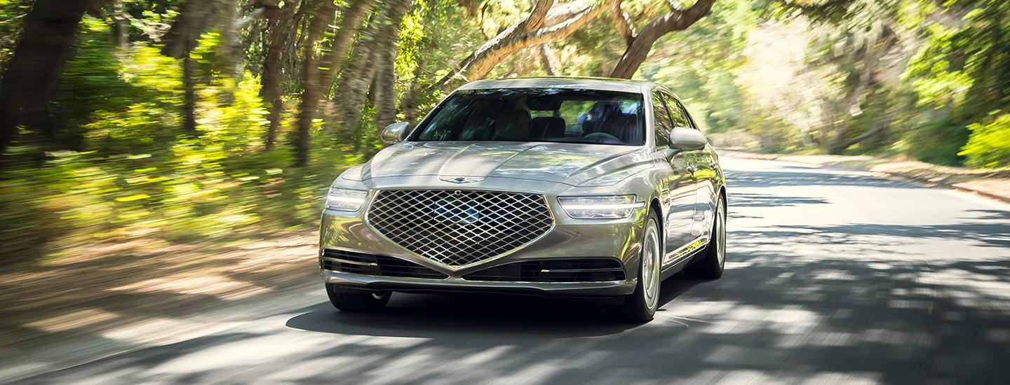 Silver 2021 Genesis G90 in motion front angle with lights on