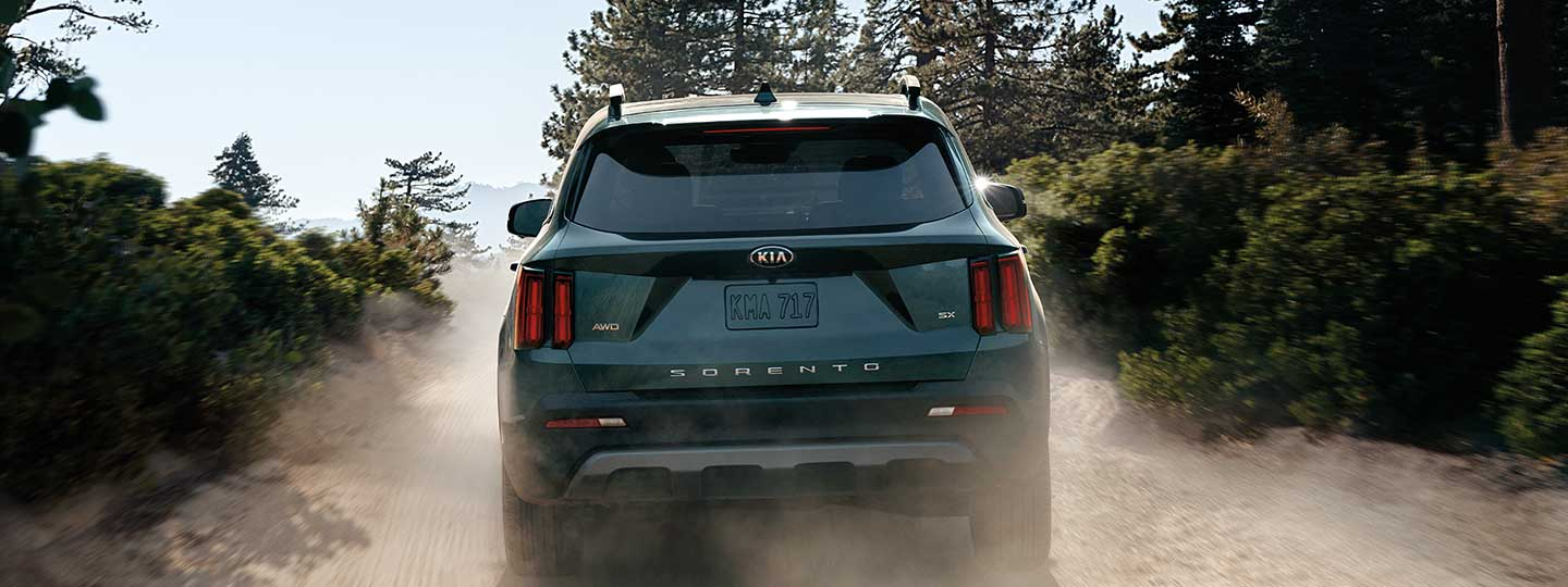Rear view of a dark gray Kia Sorento driving on a dirt road