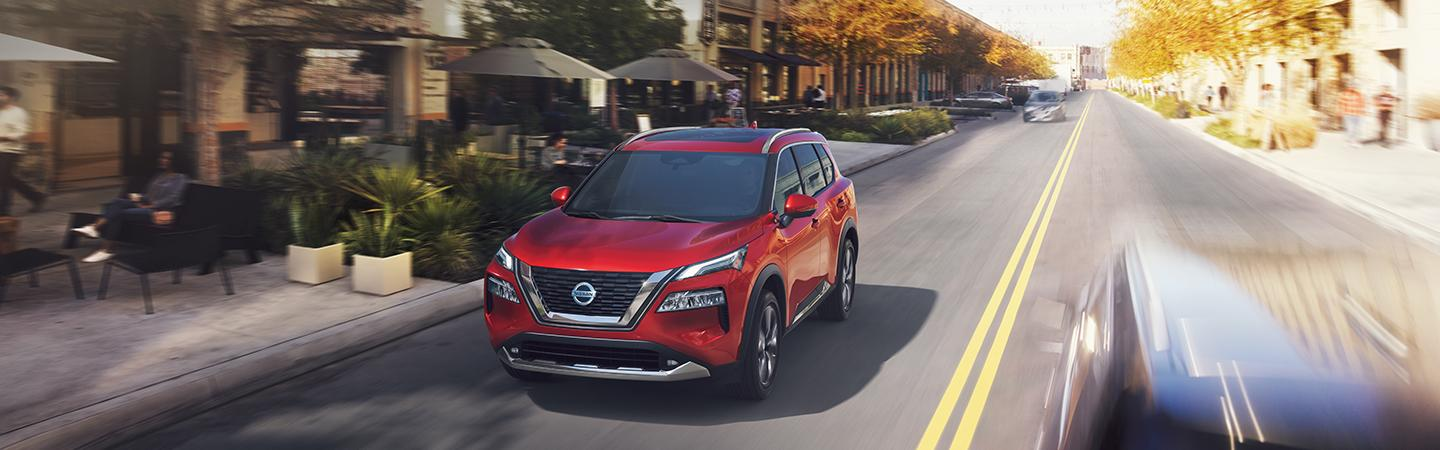 2021 Scarlet Ember Tintcoat Nissan Rogue driving downtown