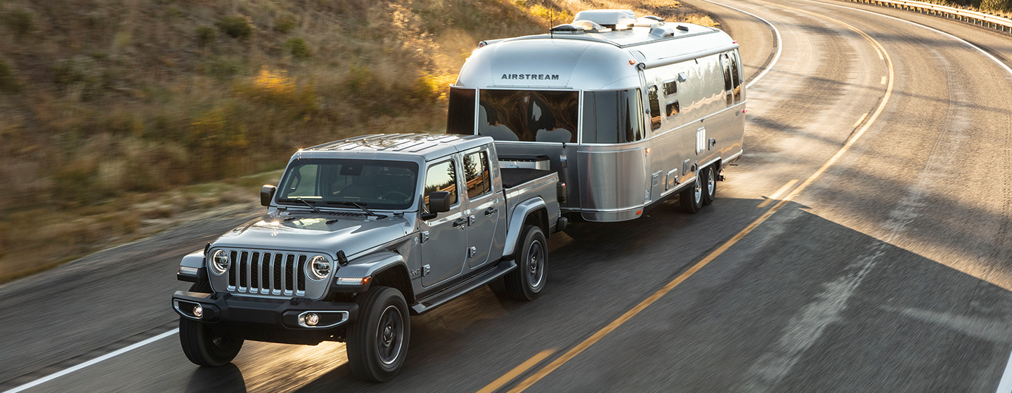 2020 Jeep Gladiator towing an Airstream on a highway.
