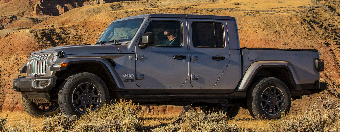Side exterior profile of the new Jeep Gladiator in a field.
