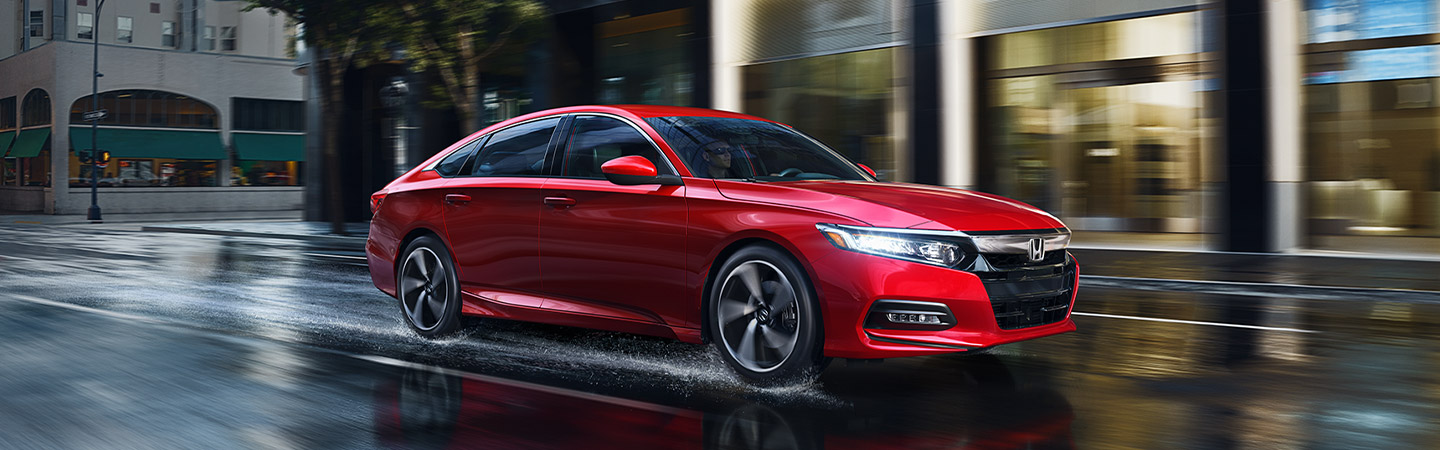 Red 2019 Honda Accord in motino driving in city in rain