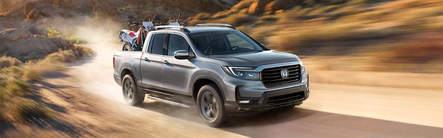 2021 Lunar Silver Metallic Ridgeline with dirt bikes loaded in the truck bed