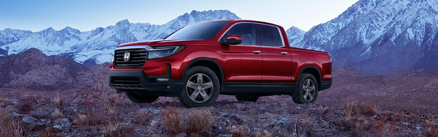 Red Metallic Ridgeline parked in front of the mountains