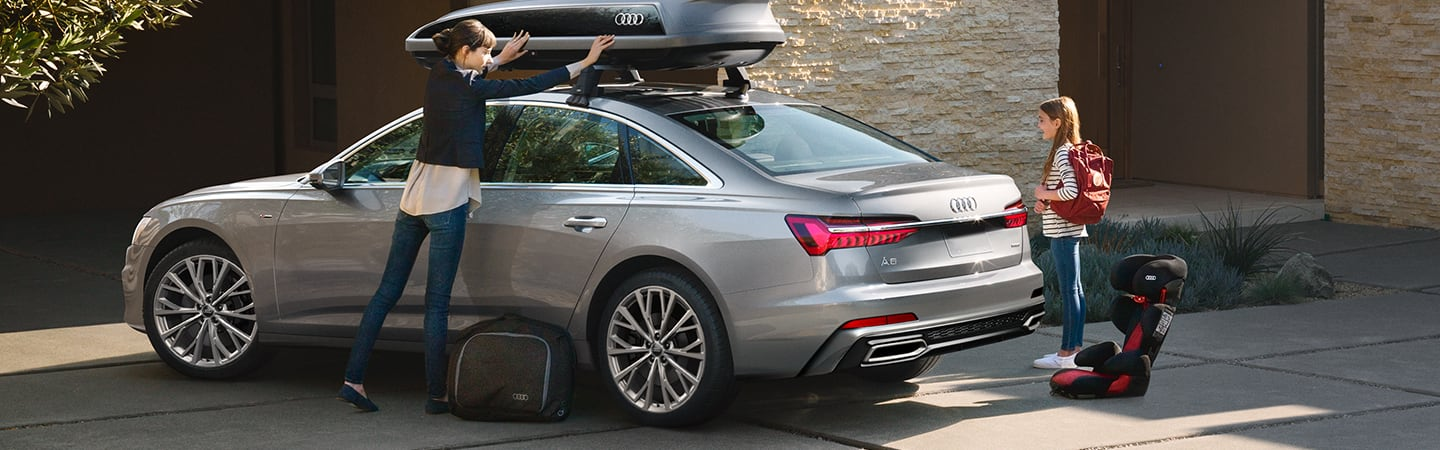 Woman loading cargo on top of silver 2020 Audi A6