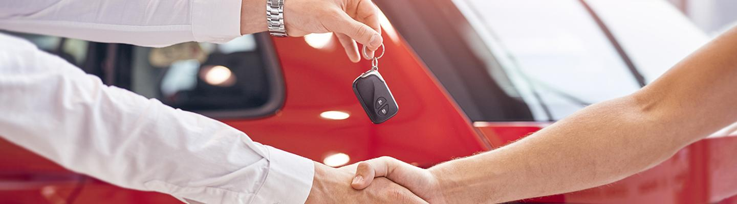 Dealership employee and customer shaking hands and exchanging car keys