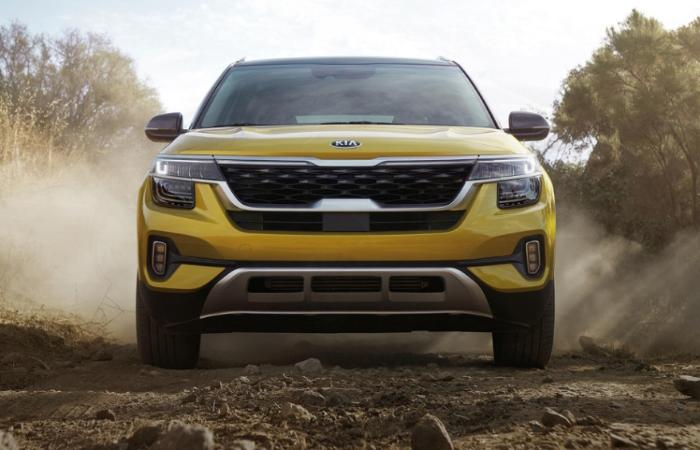 Front profile of a yellow Kia Seltos driving a dirt road