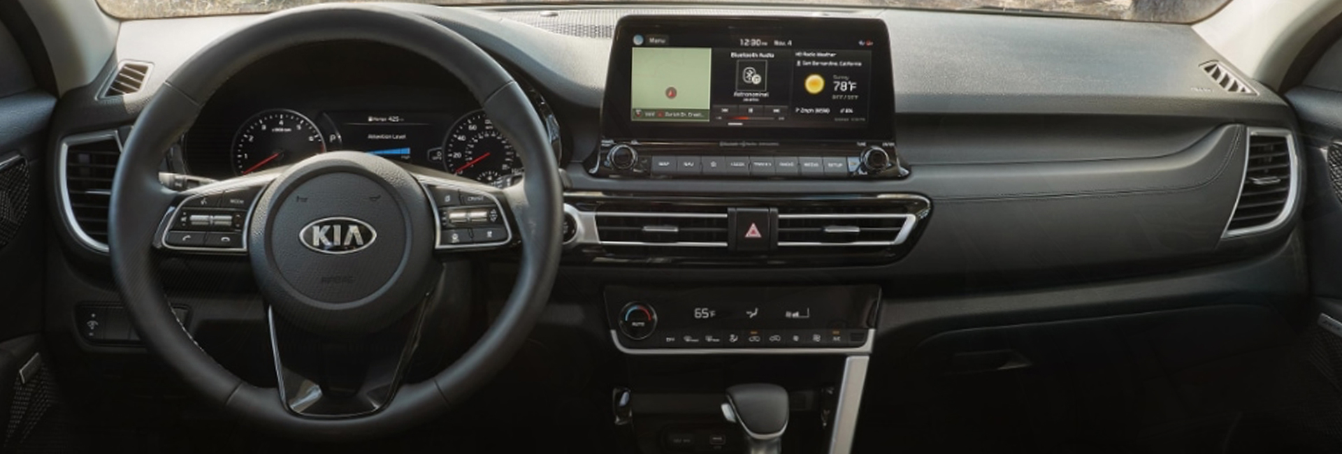 Close up view of the steering wheel and infotainment system in a Kia Seltos