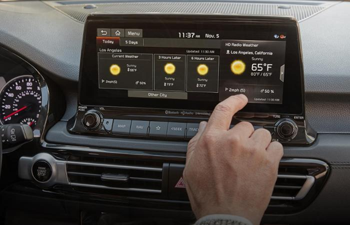Close up view of a driver using the infotainment system in their Kia Seltos