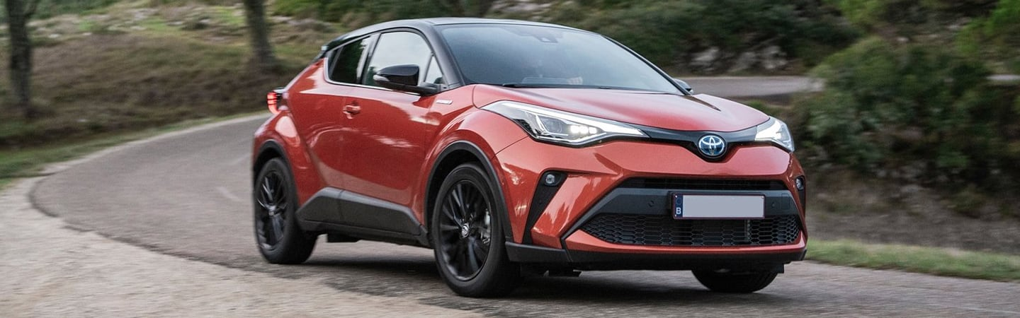 Red 2020 Toyota C-HR turning on a road