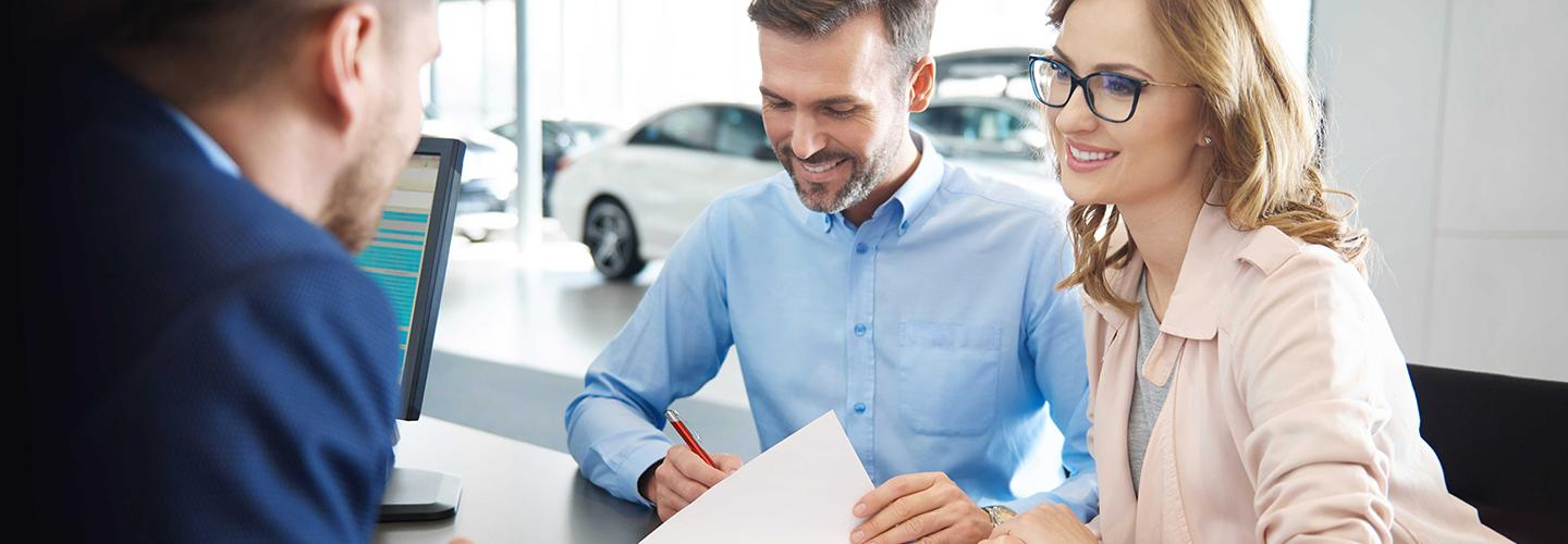 Customers reviewing financial information with a dealership employee