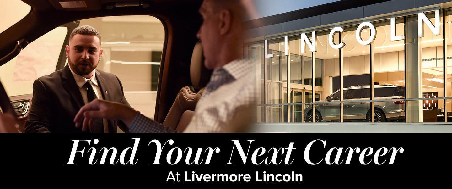 Find your next career salesman helping customer in car, view of Lincoln showrooms at Livermore Lincoln