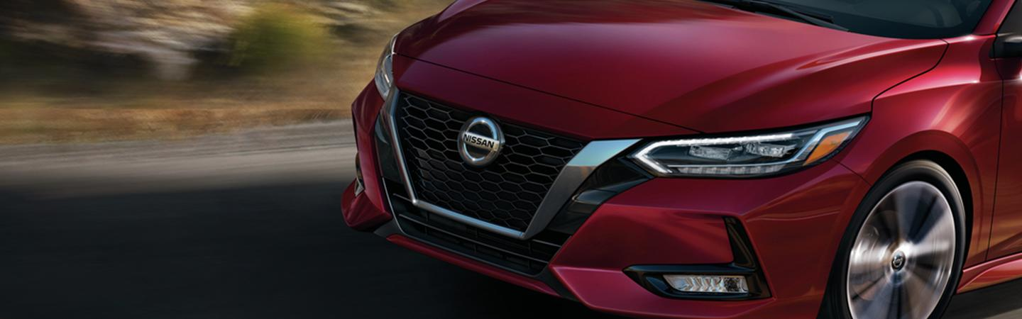 View of a V-Motion grille on  a Scarlet Ember Tintcoat 2021 Sentra