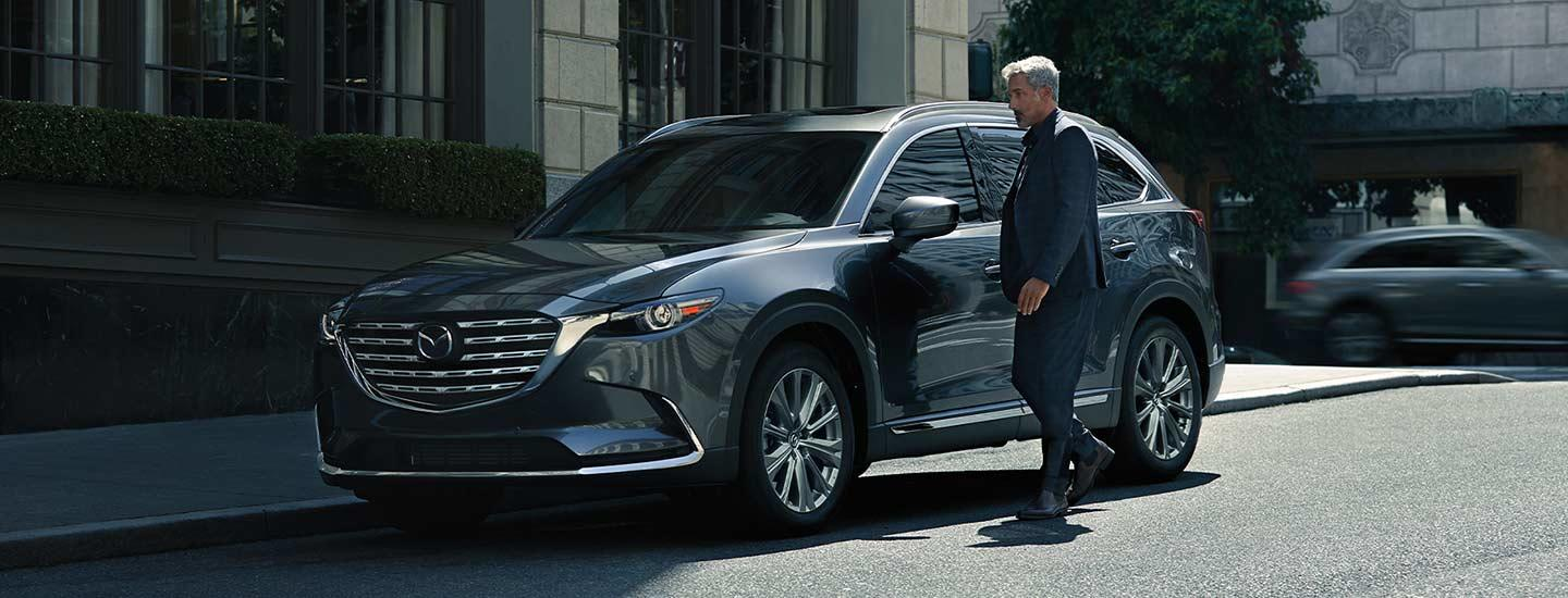 A man walking up to the 2021 CX-9