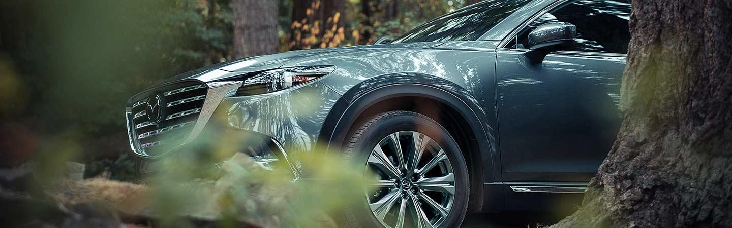 A detailed front view of the 2021 CX-9 parked in the forest