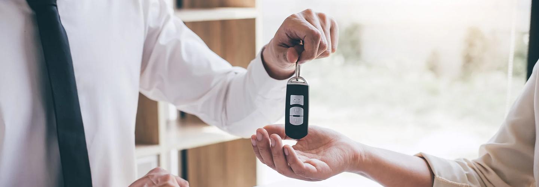Closeup view of a dealership employee handing off new car keys