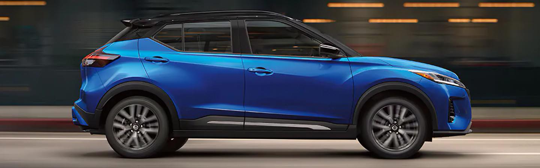 2021 Blue Metallic Nissan Kicks driving past buildings