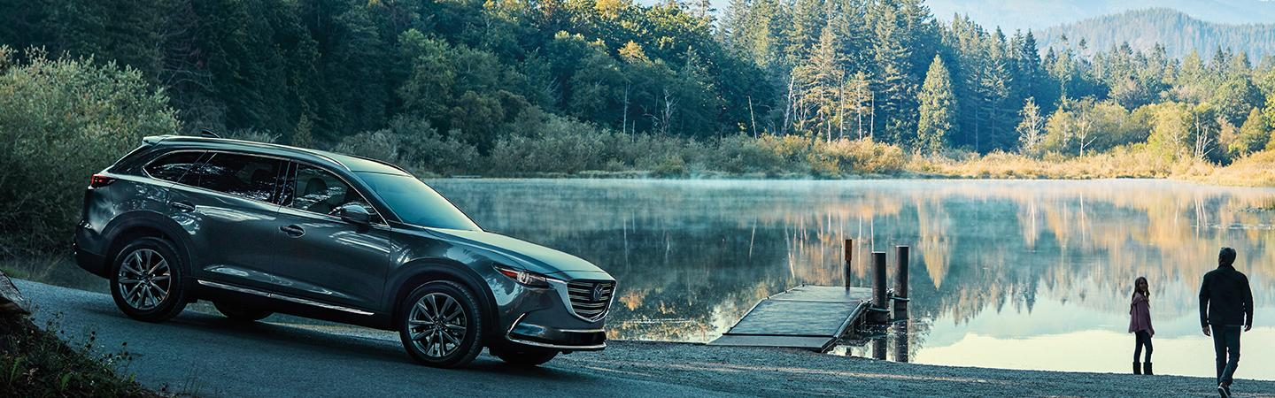 Side view of a 2020 Mazda CX-9 parked next to a lake