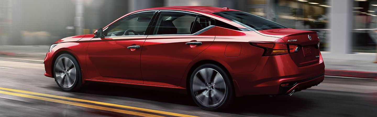 Side profile of a red Nissan Altima in motion