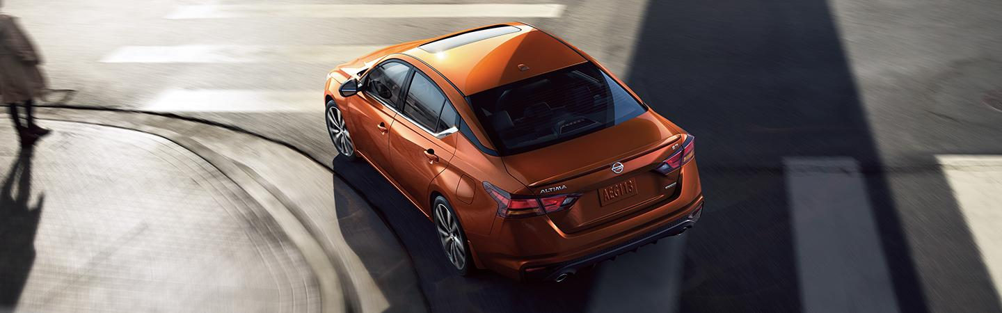 Overhead view of an orange Nissan Altima turning a corner