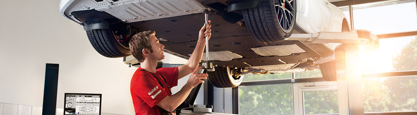Car repair service under a vehicle, available at Porsche Oklahoma City