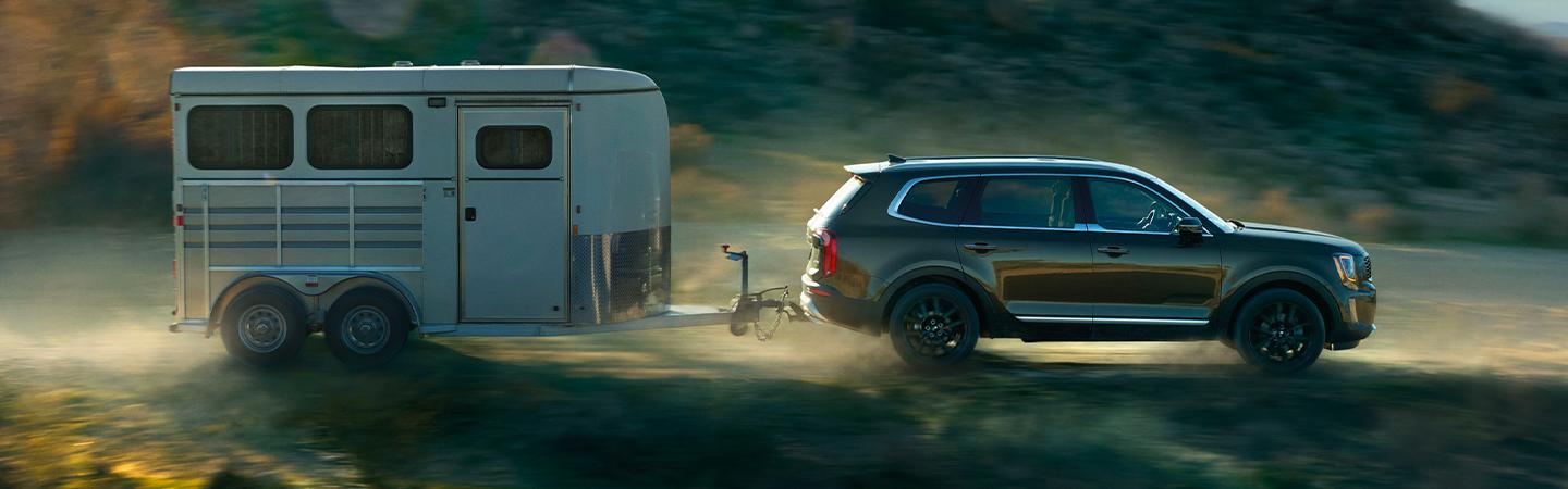 2020 Hyundai Palisade pulling classic camper on dirt road