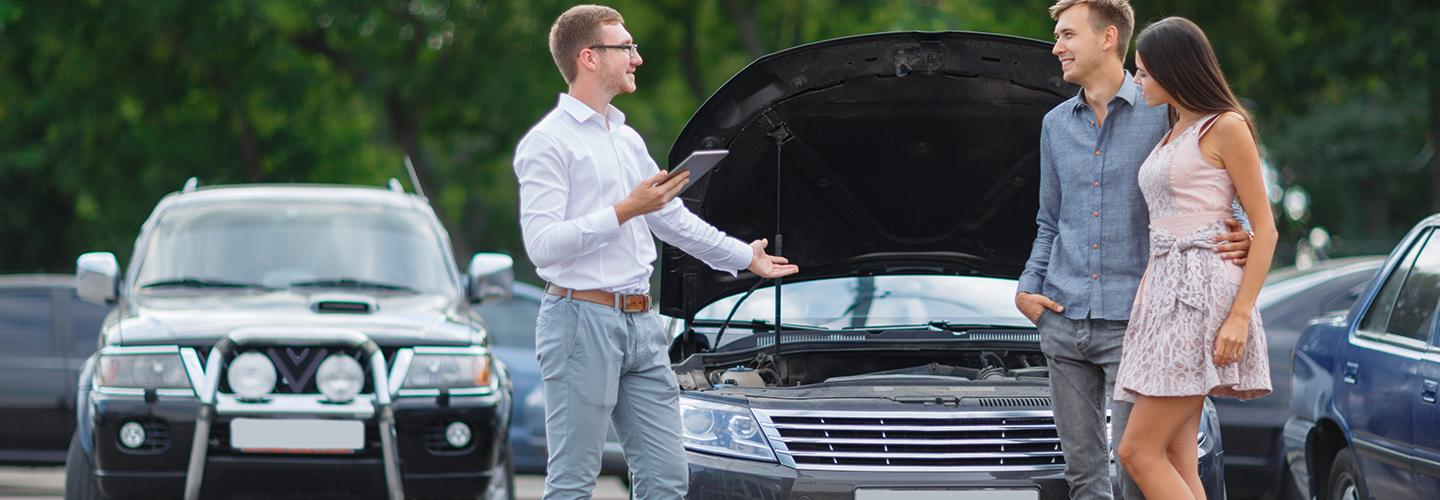 A dealership employee showing customers the inside of a vehicle