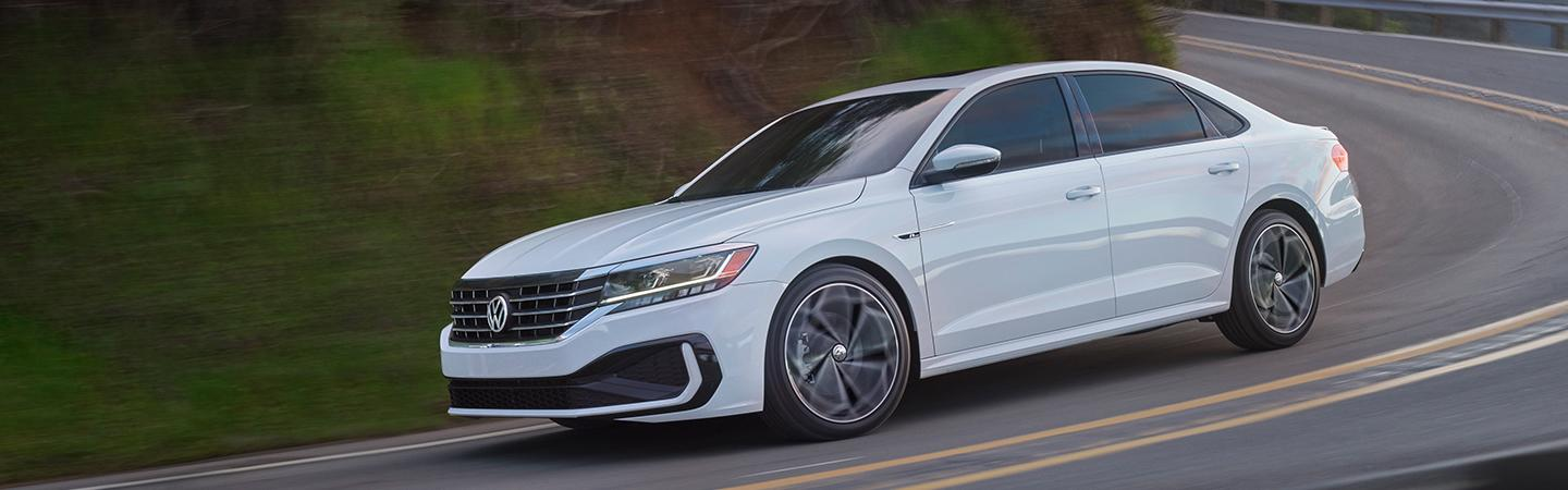 A white 2021 Passat in motion down a hill