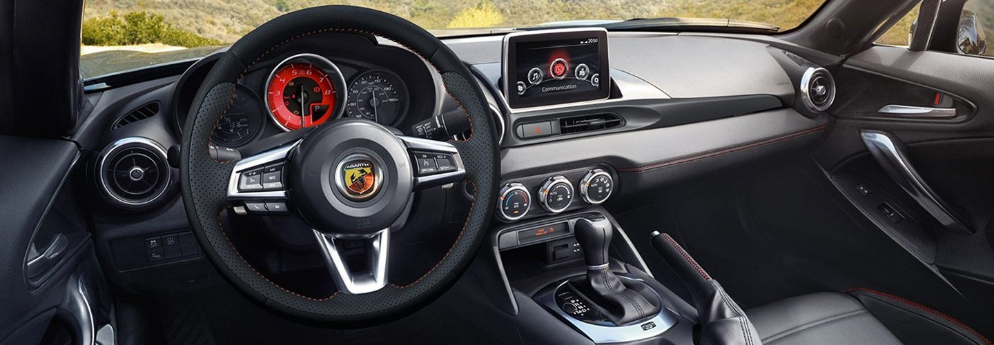 Interior steering wheel and infotainment system view of the Fiat 124 Spider