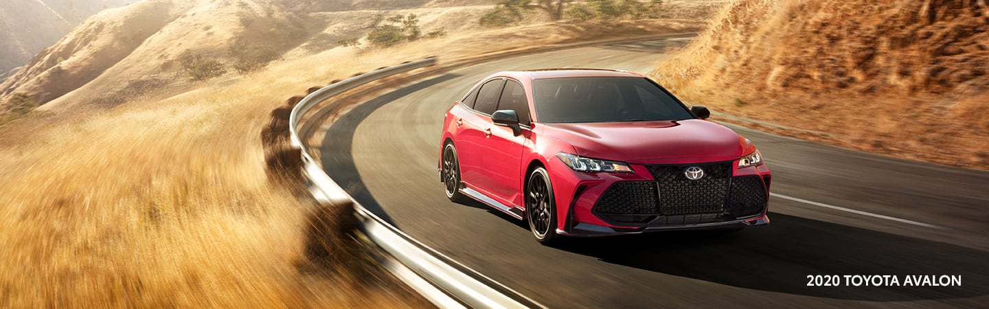 Red 2020 Toyota Avalon turning on a road