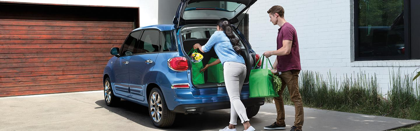 Couple unloading groceries from the trunk of the 2020 FIAT 500L