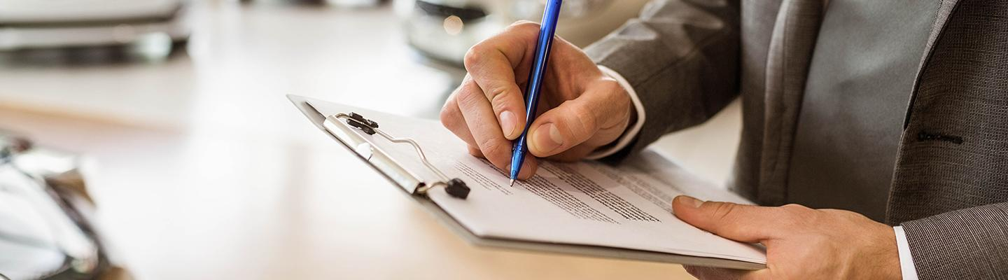 Close up view of a dealership employee writing on a clipboard