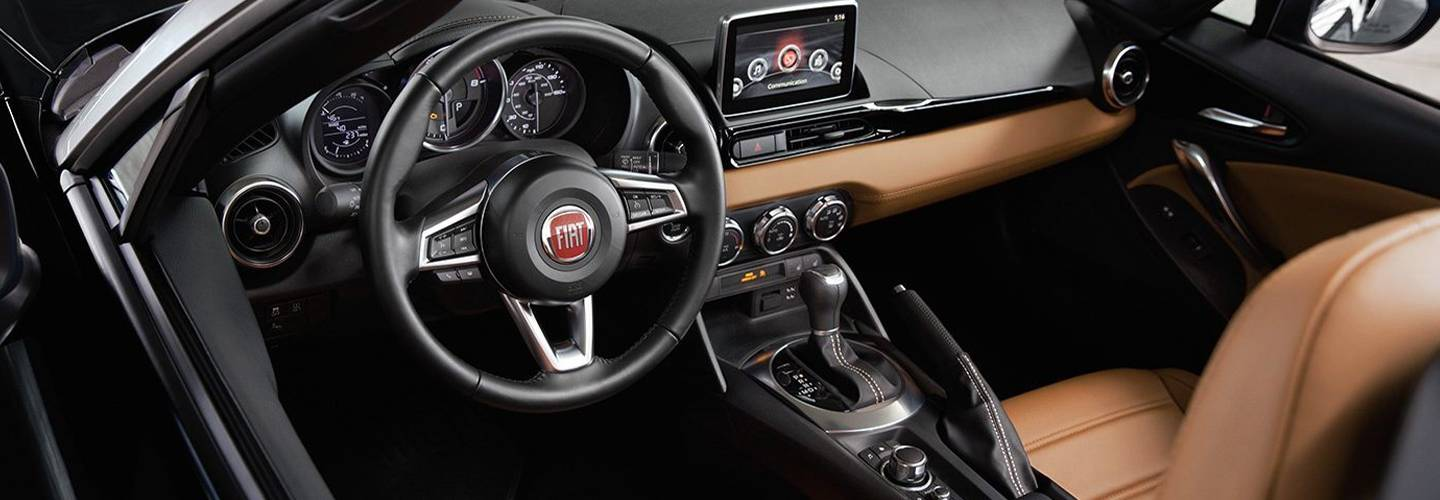 Interior view of a FIAT 124 Spider steering wheel and infotainment system