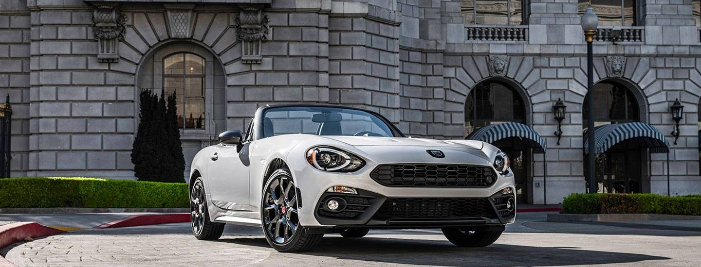 White FIAT 124 Spider parked in front of a building