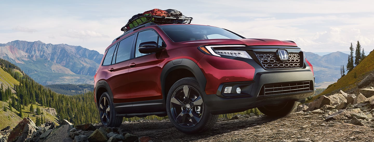 Front view of a 2020 Honda Passport driving up a hill side