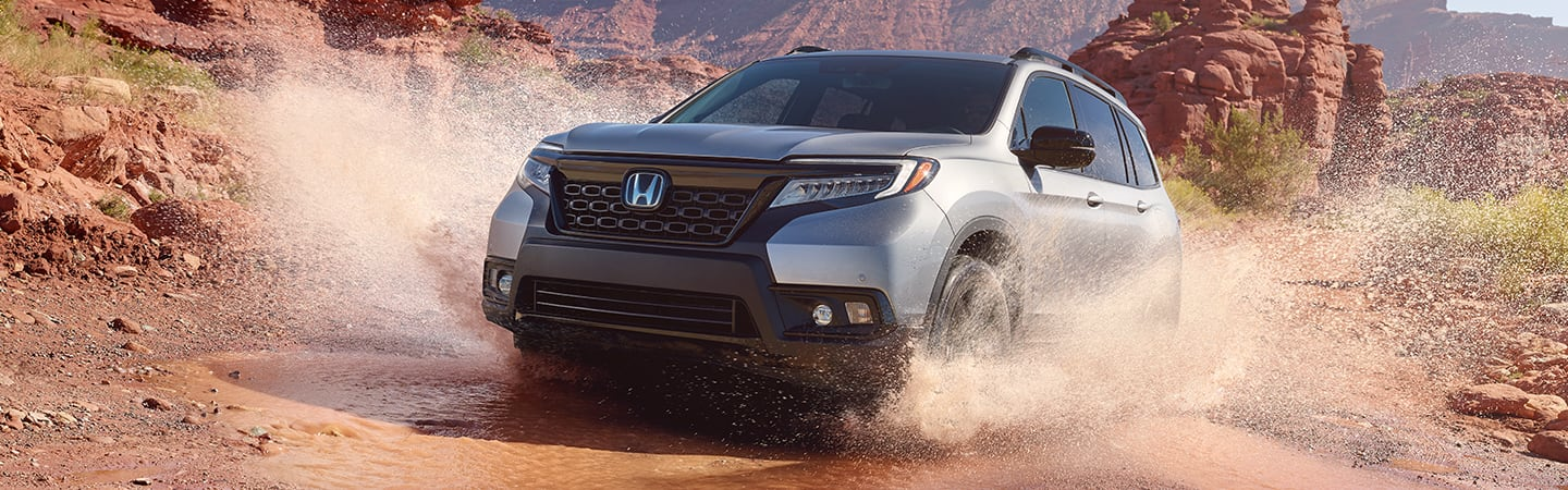 Front view of a 2020 Honda Passport driving through mud