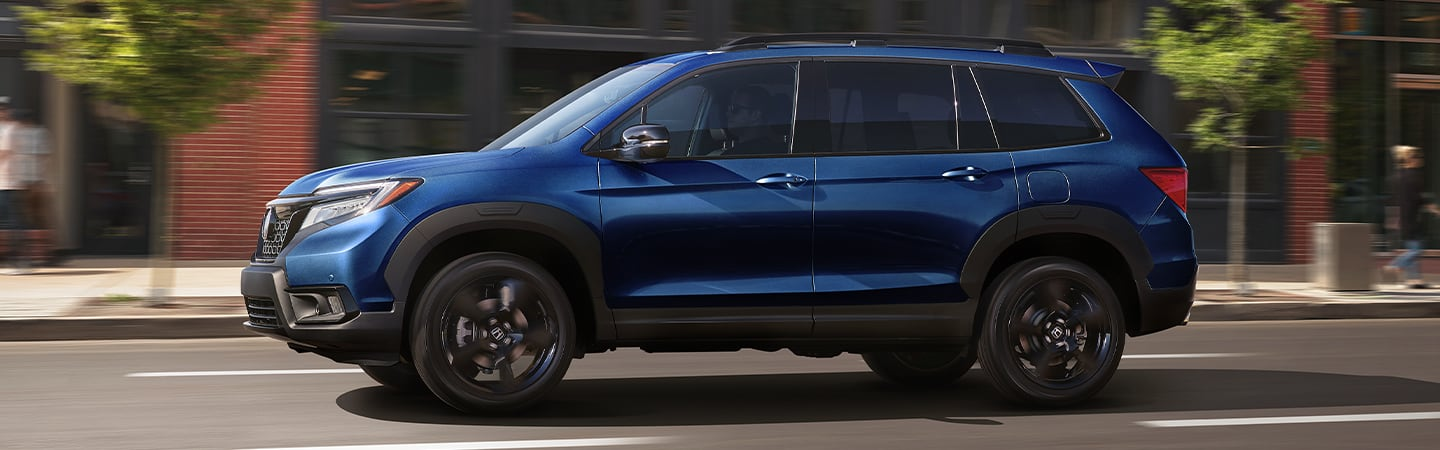Side view of a blue 2020 Honda Passport driving in the road