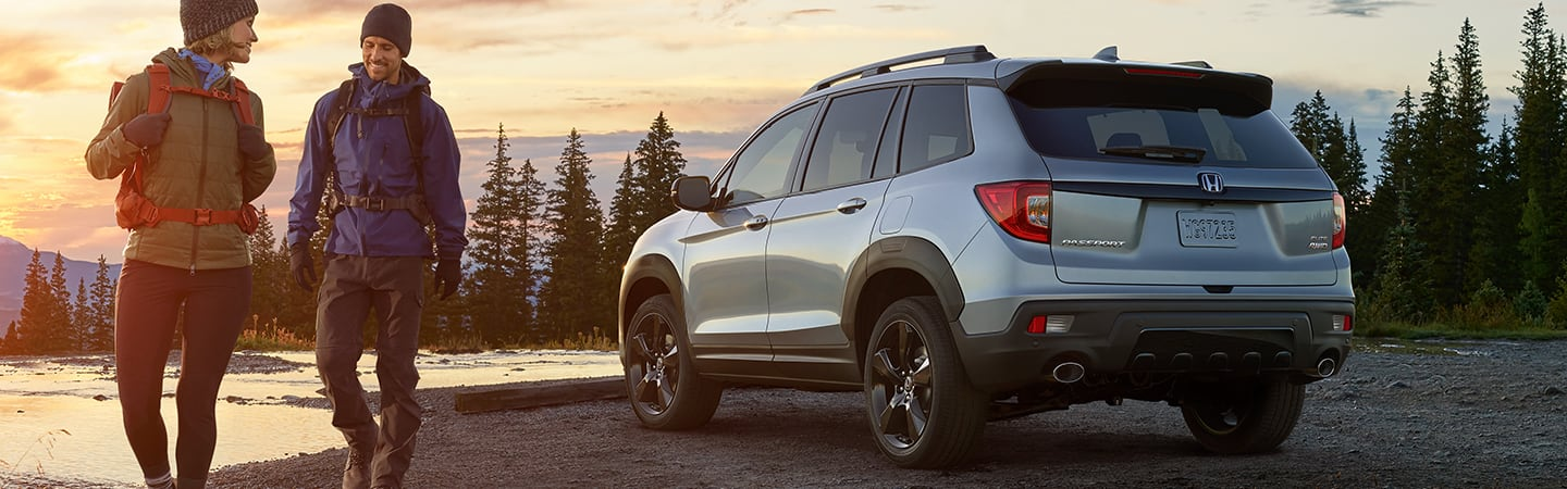 Rear view of a Silver 2020 Honda Passport parked next to a lake