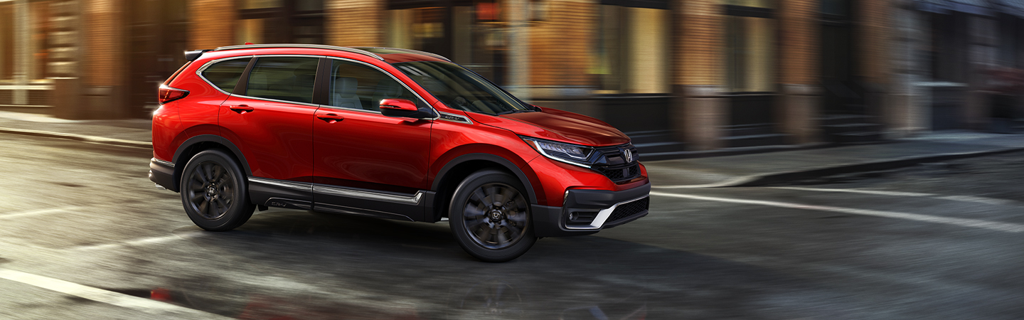 Red 2020 Honda CR-V driving in the city