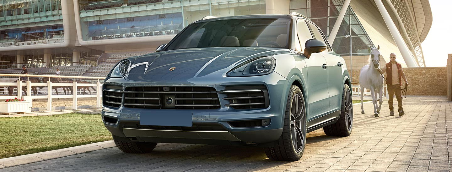 Blue Porsche Cayenne parked, man with horse walking behind