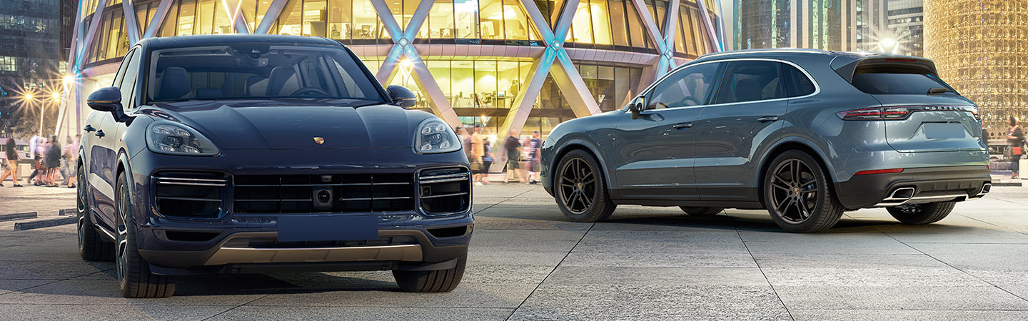 Front side of dark blue Cayenne parked; side view of light blue Cayenne parked