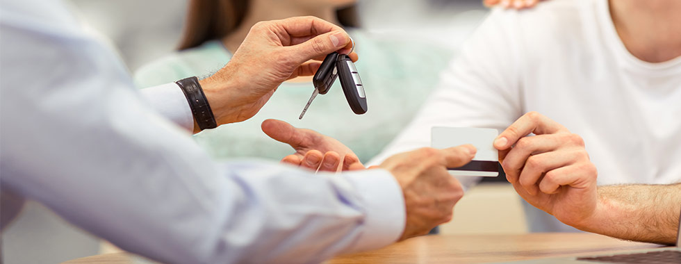 Family giving credit card to dealer for car keys