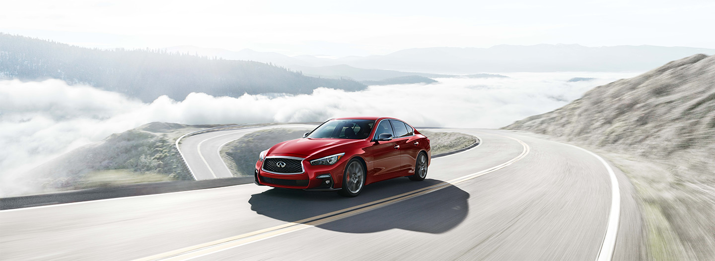 Front left side of the 2018 INFINITI Q50 driving on a bridge
