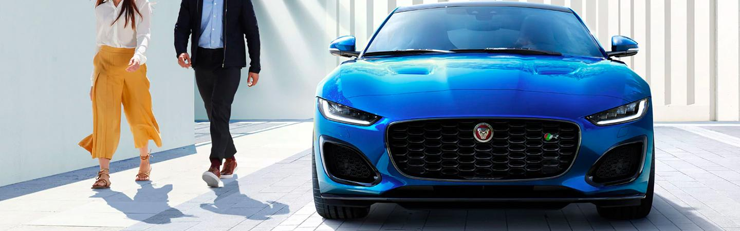 A coupe walking next to the 2021 Jaguar F-Type
